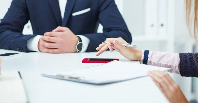 Twee personen aan tafel tijdens formele sales coaching